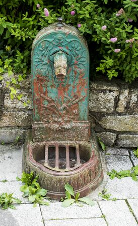 Old rusty cast iron drinking fountain with decorative pattern Stock Photo