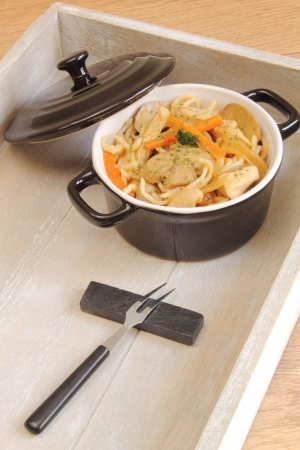 Black cooking pot with chicken noodles photo