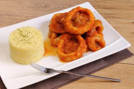 Plate of couscous with calamari in tomato sauce