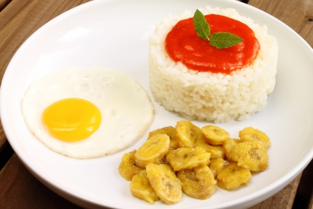 Rice Cuban style, with cooked rice, tomato sauce, fried egg and fried banana Stockfoto