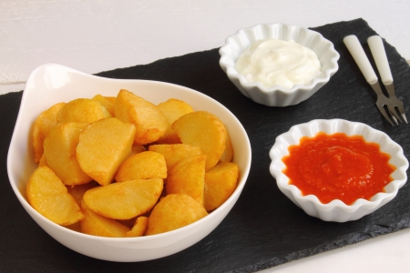 Patatas bravas is a Spanish tapa of fries with mayo and a spicy sauce photo