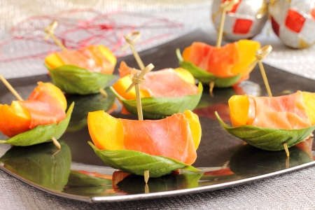 Skewered peaches with prosciutto and basil on a Christmas table Stockfoto