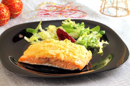 Baked salmon with almond and cheese crust on a Christmas table
