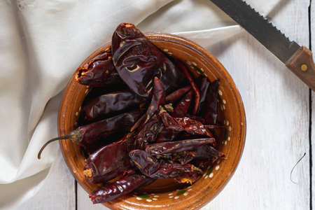 Dried chili in a clay dish with a white background and a serrated knife aside Stock fotó
