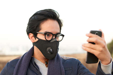 Man with blue jacket, white shirt, black glasses, mask, checking his cell phone at sunrise in autumn