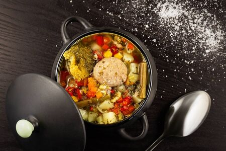 vegetable soup with meatballs in a dark tureen with a lid on a black table with scattered salt