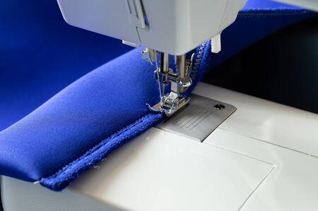 En una máquina de coser blanca producto cosido cubierta de neopreno azul disparó primer plano.