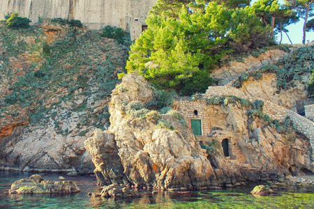 Secret doors on a cliff in front of the transparent water in Dubrovnik, Croatia.