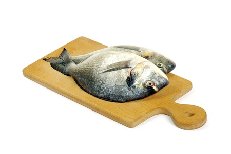 Dorado fish on wooden cutting board isolated on white photo