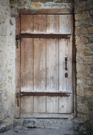 portones de madera: antigua puerta de madera en una pared de piedra Foto de archivo