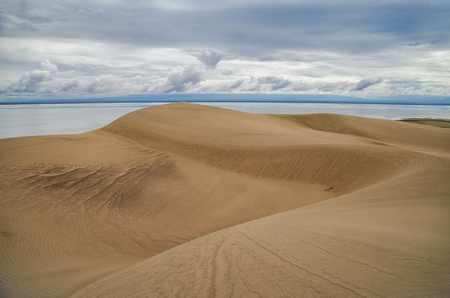 Dramatic clouds over the sand. Barkhan Mongol-Els sands and saltwater lake Dorgon. Nature and travel. Mongolia, Gobi Desert, Govi-Altai