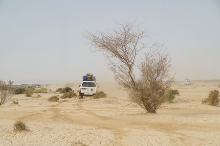 contain: Travel across Africa. African off road terrain. Dust cloud. SUVs go on the desert to the Danakil Depression. The lowlands are affected by the heat, drought, and minimal air circulation, and contain the hottest places (year-round average temperatures) of a Stock Photo