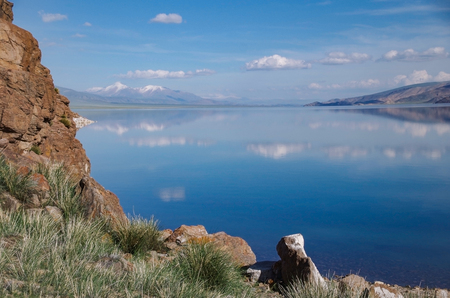 Mongolian Altai. Summer landscape. Reflection of a snow-covered mountains, colorful blue sky with clouds in a crystal clear cold water of the mountain freshwater lake. Elevation is at 2080 meters high. Nature and travel. Mongolia, lake Tolbo