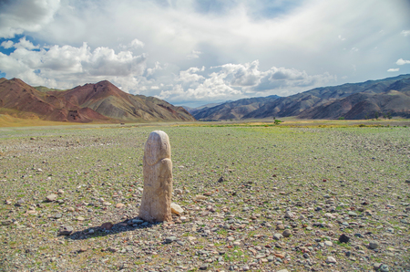 Mongolian Altai. Turkic stone warrior with a rough image of a human face. Kurgan stelae (Balbal). Anthropomorphic stone stelae, image cut from stone, installed atop kurgan. Nature and travel. Mongolia, Bayan-Olgii Province