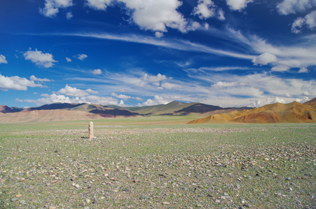 Mongolian Altai. Scenic view of the turkic stone warrior (kurgan stelae or balbal) against the background of the multicolor mountains and amazing sky. Nature and travel. Mongolia, Bayan-Olgii Province