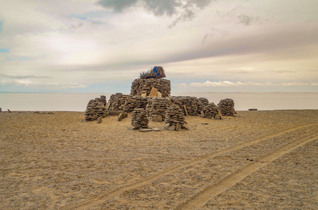 Sacred stone heaps. Altars or shrines in Mongolian folk religious practice. Sites for the worship. Ovoo at the southern shore of the saltwater Dorgon Lake. Nature and travel. Mongolia, Great Lakes Depression, Govi-Altai Province Stock Photo