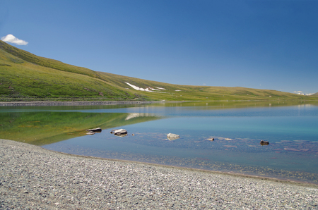 Mongolian Altai. Scenic summer landscape of highland lake. Beautiful reflection in crystal clear cold water. Nature and travel. Mongolia, Bayan-Olgii Province Stok Fotoğraf