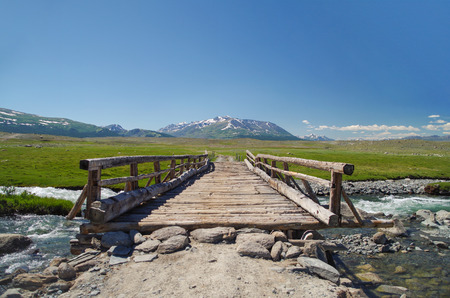 Mongolian Altai. Log bridge through the raging mountain river. High water. Spring run-off. Nature and travel. Mongolia, Bayan-Olgii Province, Altai Tavan Bogd National Park Stok Fotoğraf