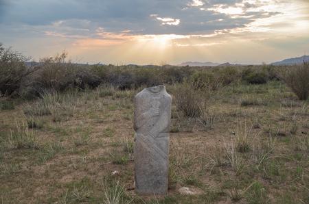 Mongolian Altai. Past civilizations. Turkic Stone Man. Scenic view of the Turkic stone warrior (kurgan stelae  balbal) on sunset. Nature and travel. Mongolia