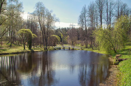 Sunny day. Beautiful spring landscape. White wooden footbridge through the pond. Nature and travel. Russia, Pskov Oblast, historical Pushkin places Stok Fotoğraf