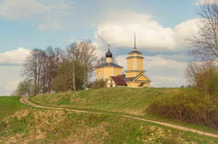 Beautiful evening. Spring landscape. Yellow wooden church. Pushkin places. Russia, Pskov Oblast