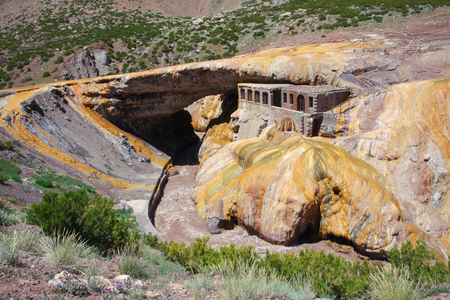 Puente del Inca. Natural arch that forms a bridge over the river, hot springs and abandoned spa building. Andes or Andean Mountains. Argentina, Mendoza Province, Chile.