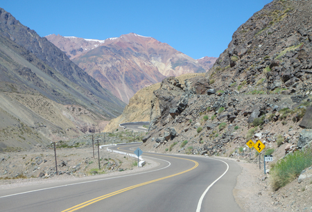 Scenic view of winding road. Empty road. Warning signs. Andes or Andean Mountains. Argentina, Mendoza Province, Chile
