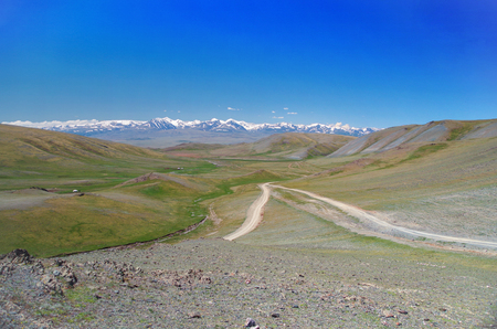 Mongolian Altai. Mountain pass. Scenic valley on the snowcapped mountains. Beautiful view of the dirt road. Nature and travel. Mongolia, Bayan-Olgii Province