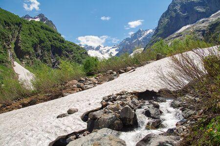 Dombay. Trek to Sofrudzhu Falls. Beautiful view of the snowfields, river and mountains. Nature and travel. Russia, North Caucasus, Karachay-Cherkessia Stok Fotoğraf