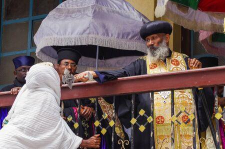 Addis Ababa, Ethiopia - Jan 02, 2014: Holytide. Minister wearing ceremonial robe. Parishioner kissing cross. Publikacyjne
