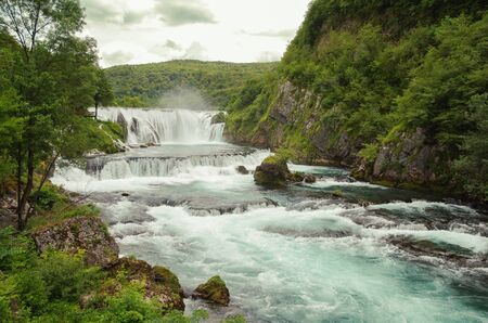 Waterfall Strbacki buk and rapids on the river Una. Natural landscape of exceptional beauty. Typical karst spring of upward type, of special green-blue color. On the border between Croatia and Bosnia  写真素材