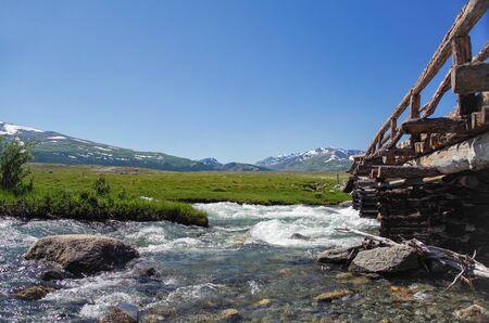 Mongolian Altai. Log bridge through the raging mountain river. High water. Spring run-off. Nature and travel. Mongolia, Bayan-Olgii Province, Altai Tavan Bogd National Park 写真素材