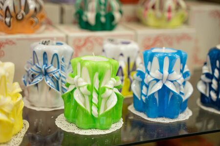 handmade multi-colored wax candles standing on a glass stand