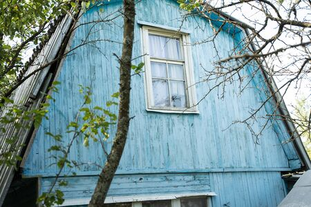 old two-story blue house standing next to a tree Stock Photo