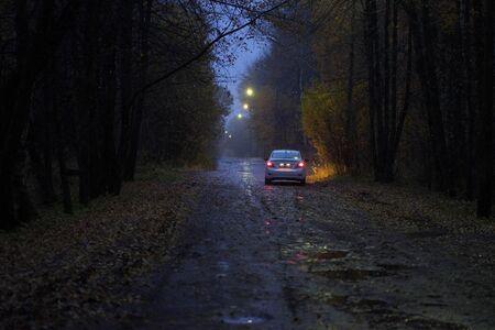 samochód z reflektorami na jesiennej drodze