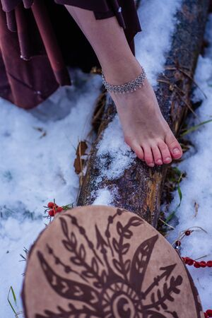 female leg on a log and a tambourine on a snow background