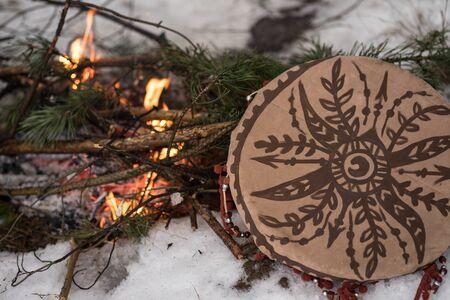 brown shaman's tambourine and bonfire made of fir