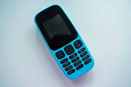 blue push-button cell phone with black buttons