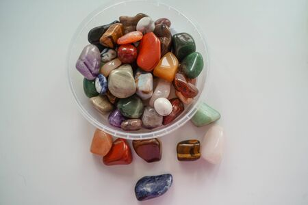 multi-colored pebbles on a white background and in daylight