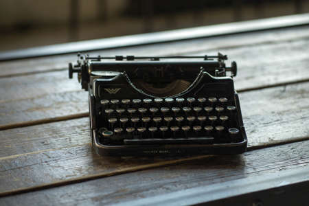 a typewriter stands on a wooden table