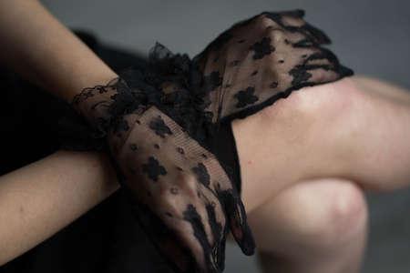 female hands in black lace gloves lie on her knees