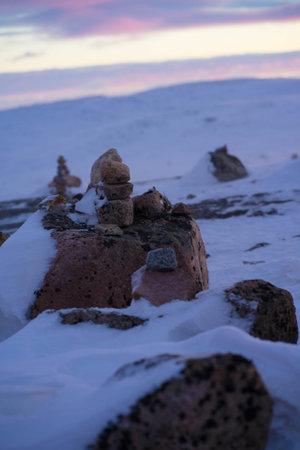 stones are heaped in the snow near the road at dawn Foto de archivo