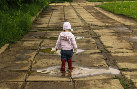 The child runs through puddles in rubber boots