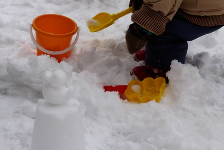 Child plays with snow and molds