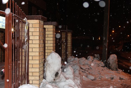 Snow-covered fence during a night snowfall