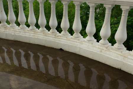 Balusters of rounded handrails with reflection in water