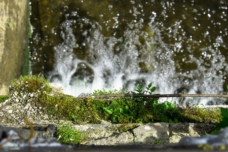 Parapet overgrown with moss over a waterfall photo