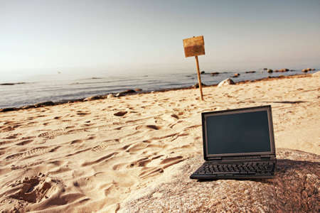 sin: Single black laptop and woodens sin in background alone at beach.