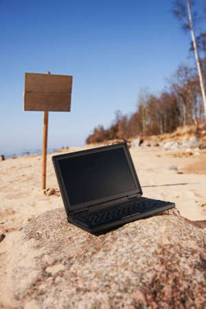Single black laptop and wooden sign i background alone in beach. Stock Photo - 4776671