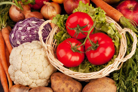 Pile of vegetables. Three tomatoes in basket, lettuce, onions, carrots, half of cabbage, cauliflower and potatoes. photo